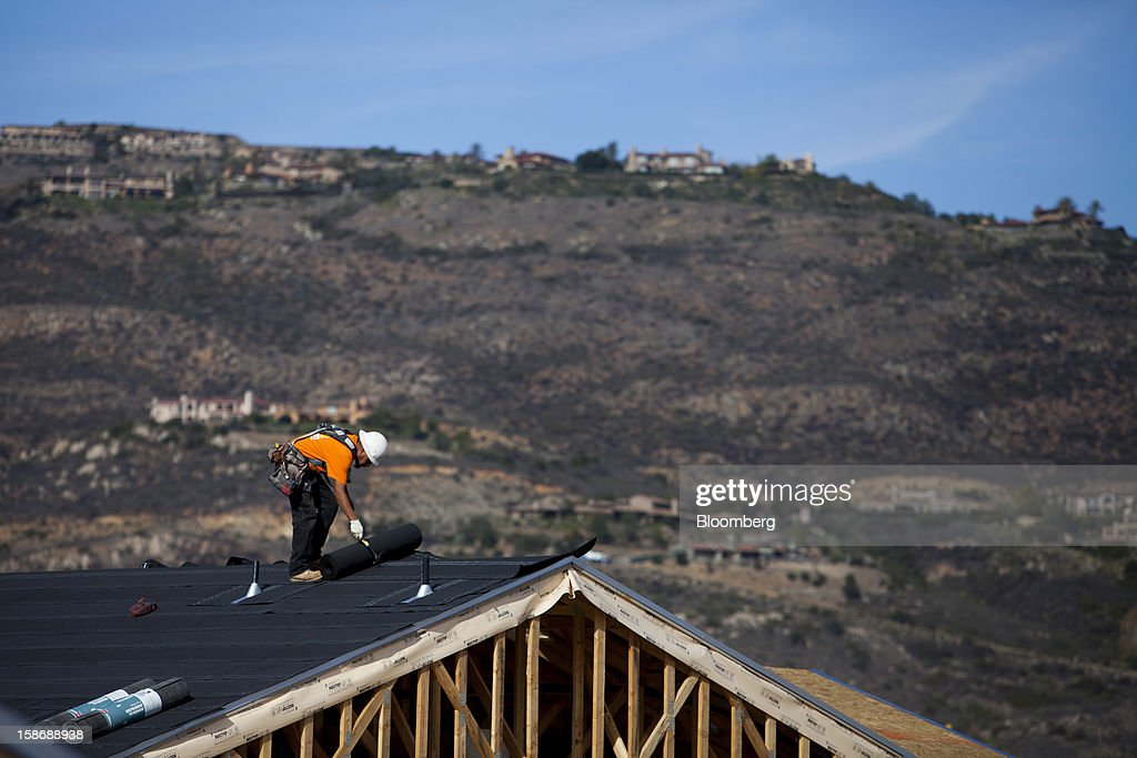 A worker installs roofing material on a house under construction at Davidson Communities LLC's Arista at The Crosby development in Rancho Santa Fe, California, U.S., on Friday, Dec. 21, 2012. New home sales climbed to a 380,000 annual rate in November, the most since April 2010, according to the median forecast of 60 economists surveyed by Bloomberg before Dec. 27 figures from the Commerce Department. Photographer: Sam Hodgson/Bloomberg via Getty Images