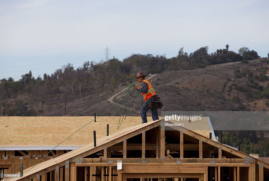 A worker installs roofing material on a house under construction at Davidson Communities LLC's Arista at The Crosby development in Rancho Santa Fe, California, U.S. on Friday, Dec. 21, 2012. New home sales climbed to a 380,000 annual rate in November, the most since April 2010, according to the median forecast of 60 economists surveyed by Bloomberg before Dec. 27 figures from the Commerce Department. Photographer: Sam Hodgson/Bloomberg via Getty Images