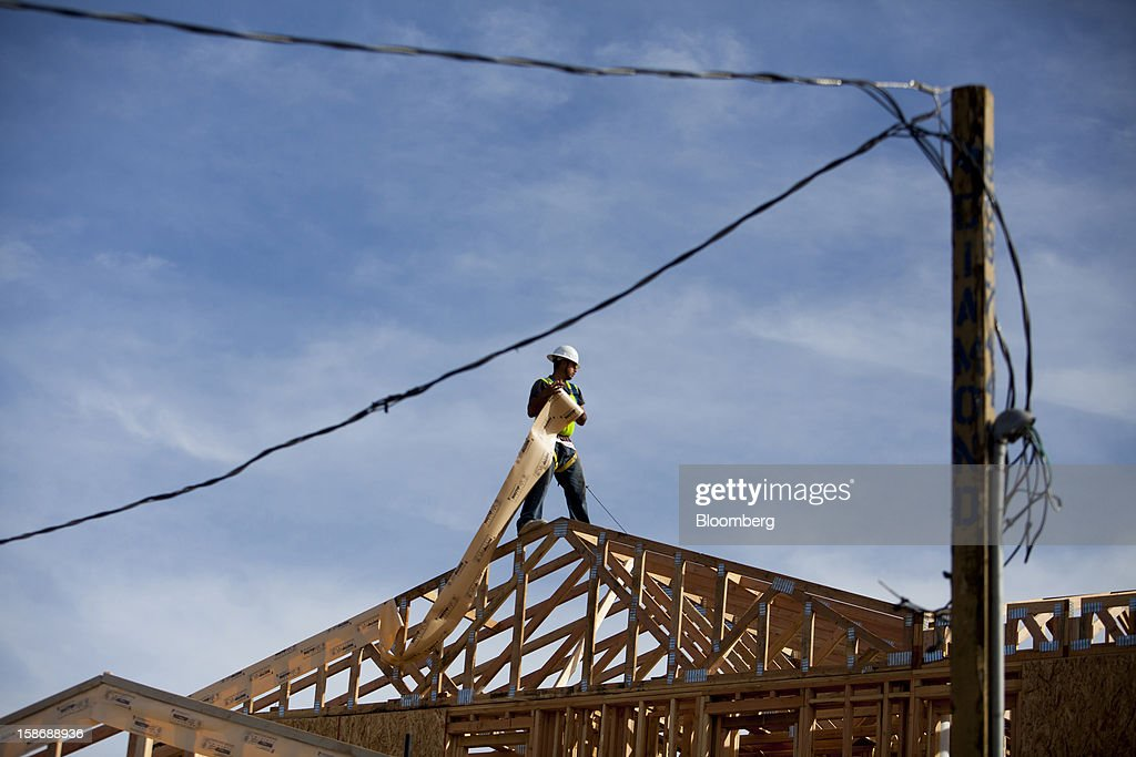 A worker installs roofing material while standing on the roof a house under construction at Davidson Communities LLC's Arista at The Crosby development in Rancho Santa Fe, California, U.S., on Friday, Dec. 21, 2012. New home sales climbed to a 380,000 annual rate in November, the most since April 2010, according to the median forecast of 60 economists surveyed by Bloomberg before Dec. 27 figures from the Commerce Department. Photographer: Sam Hodgson/Bloomberg via Getty Images
