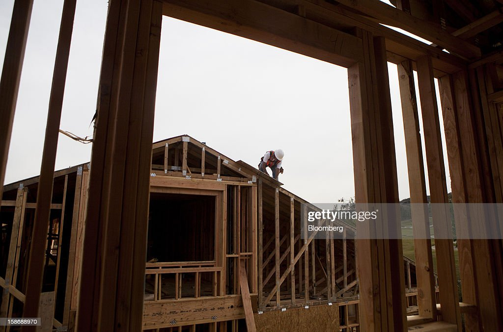 A worker installs the roof of a house under construction at Davidson Communities LLC's Arista at The Crosby development in Rancho Santa Fe, California, U.S., on Friday, Dec. 21, 2012. New home sales climbed to a 380,000 annual rate in November, the most since April 2010, according to the median forecast of 60 economists surveyed by Bloomberg before Dec. 27 figures from the Commerce Department. Photographer: Sam Hodgson/Bloomberg via Getty Images