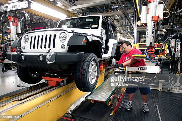 A worker installs tires on a 2014 Jeep Wrangler as it undergoes assembly at the Chrysler Toledo North Assembly Plant Jeep May 7 2014 in Toledo Ohio...