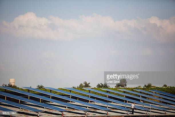A worker instals photovoltaic solar panels to create electricity from the sun on the roof of a chicken coop November 15 2009 in the village of Ein...