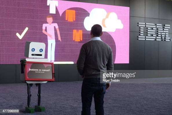 A worker interacts with a roboter at the IBM stand at the 2014 CeBIT technology trade fair the day before the fair opens to visitor on March 9 2014...
