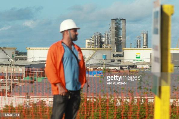 A worker is backdropped by the Abreu e Lima refinery under construction at the Suape industrial complex of the Brazilian state oil company Petrobras...