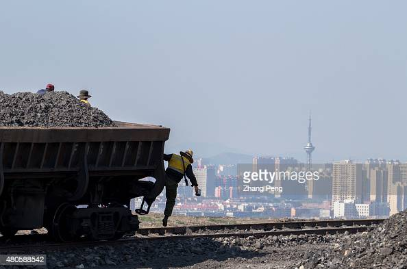 A worker is jumping down from the steam locomotive which will dump the coal cinders beside the rail The waste coal cinders have heaped up to form a...