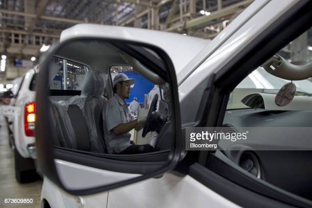 A worker is reflected in a mirror as he installs a component into a Nissan Motor Co Navara pickup truck on an assembly line at the company's plant in...