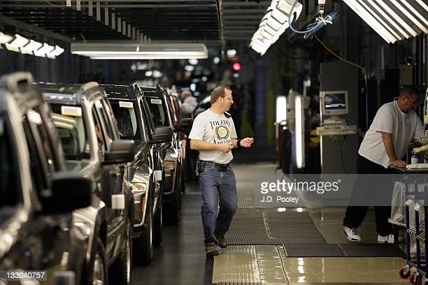 A worker is seen as Jeep Liberties and Dodge Nitros roll off the assembly line at the Toledo Assembly Complex on November 16 2011 in Toledo Ohio...
