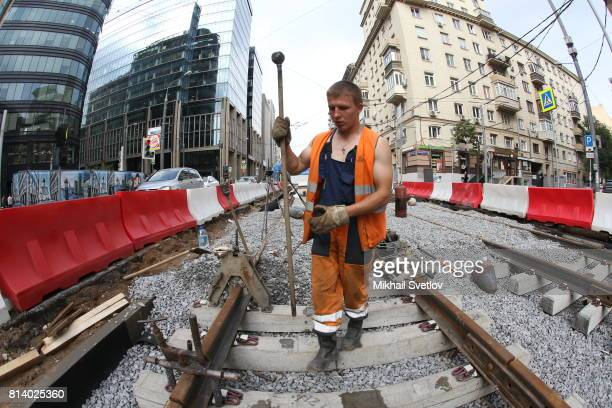 A worker is seen at construction of new tram tracks in front of Moscow Smolenskaya Railways Station July 13 2017 in Moscow Russia The Russian rouble...