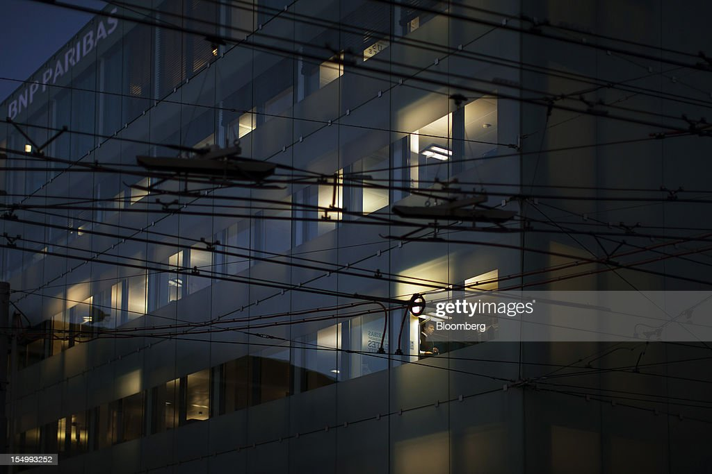 A worker is seen standing at the window of the BNP Paribas SA office in Geneva, Switzerland, on Monday, Oct. 29, 2012. Geneva's banks employed 502 fewer people at the end of June compared with a year earlier as foreign wealth managers cut jobs and shifted employees to other locations, a survey by the city's financial lobby group shows. Photographer: Valentin Flauraud/Bloomberg via Getty Images