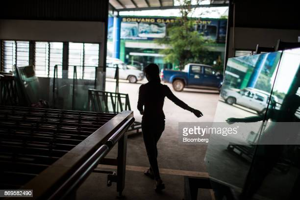 A worker is silhouetted as she walks through the Somvang Glass Factory on the outskirts of Vientiane Laos on Wednesday Nov 1 2017 Asia'ssmallest...