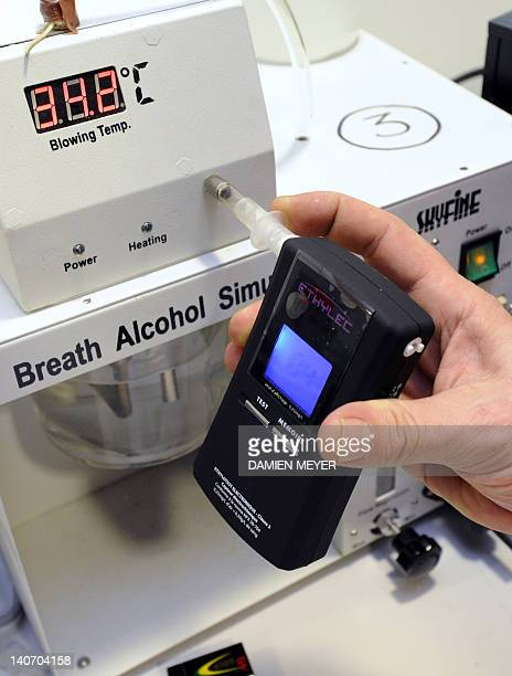 A worker is testing an electronic breathalyser in a simulator at the 'Objectif prévention' plant in Sartilly western France on March 2 2012 All...
