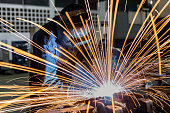 worker is welding assembly automotive part in car factory