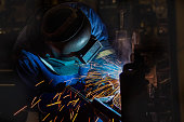 worker is welding automotive part in factory