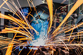 Worker is welding in car factory