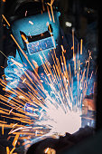 Worker is welding in factory