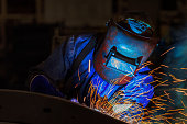 worker is welding repair automotive part in car factor