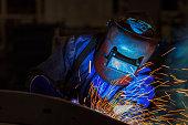 worker is welding repair automotive part in car factor