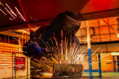 Worker is welding steel part in car factory