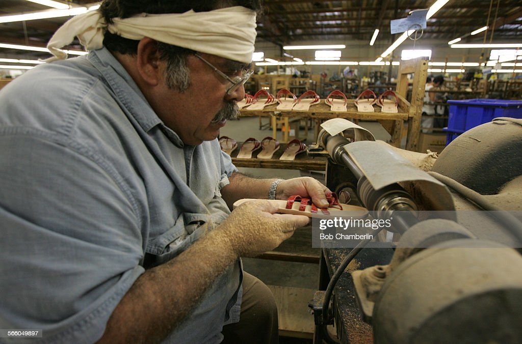 Worker Jose Contrares works roughing up soles of 'Callisto' brand shoes to prepare them for glueing at the J and A Shoe Company and Factory on 146th...