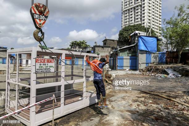 A worker jumps from a rescue basket at the excavation site of a launching shaft for Metro Line 3 operated by the Mumbai Metro Rail Corp in the...