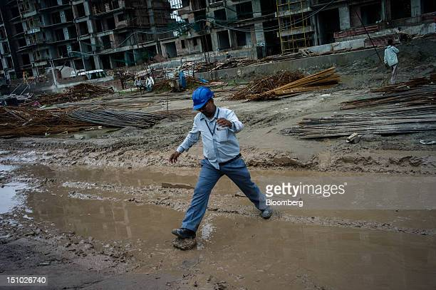A worker jumps over a puddle on the construction site of a housing block in Sector 105 of Noida in Uttar Pradesh India on Thursday Aug 30 2012...