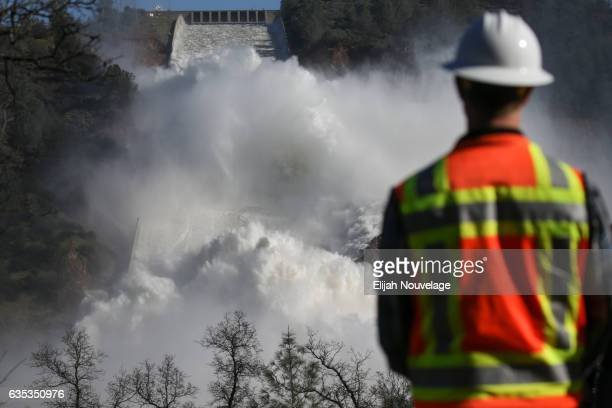 A worker keeps an eye on water coming down the damaged main spillway of the Oroville Dam on February 14 2017 in Oroville California More than 188000...