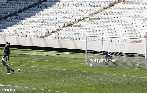 A worker kicks a penalty to score against goalkeeper Cassio at the end of the first official practice carried out at the Arena de Sao Paulo stadium...