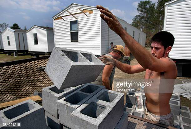 Worker Kody Johnson of Beaver Mobile Home Transport in Laurel Mississippi throws cinderblocks on the back of a truck used to stablize the delivered...