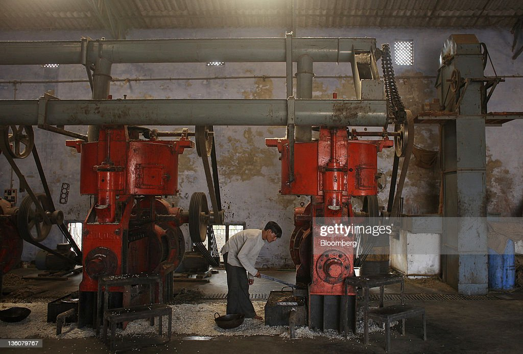 A worker labors in a factory which produces oil from cotton seed in Wankaner, India, on Sunday, Dec. 18, 2011. Cotton sales by growers in India, the second-biggest producer, declined 26 percent in the season that began Oct. 1, according to the Cotton Corp. of India, the nation's biggest buyer. Photographer: Adeel Halim/Bloomberg via Getty Images
