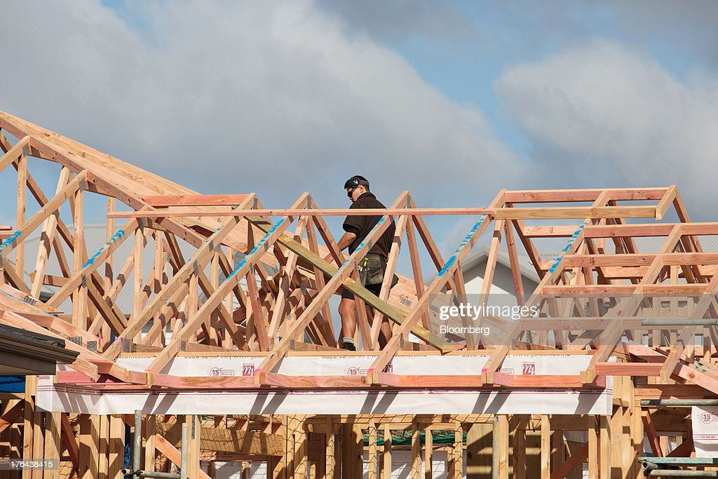 A worker labors on a house under construction in the suburb of Hobsonville Point in Auckland, New Zealand, on Tuesday, Aug. 13, 2013. New Zealand's growth rate is forecast to outpace Australia's for the next two years, helping stem an exodus that's resulted in the highest proportion of its people living overseas in the developed world after Ireland. Photographer: Brendon O'Hagan/Bloomberg via Getty Images