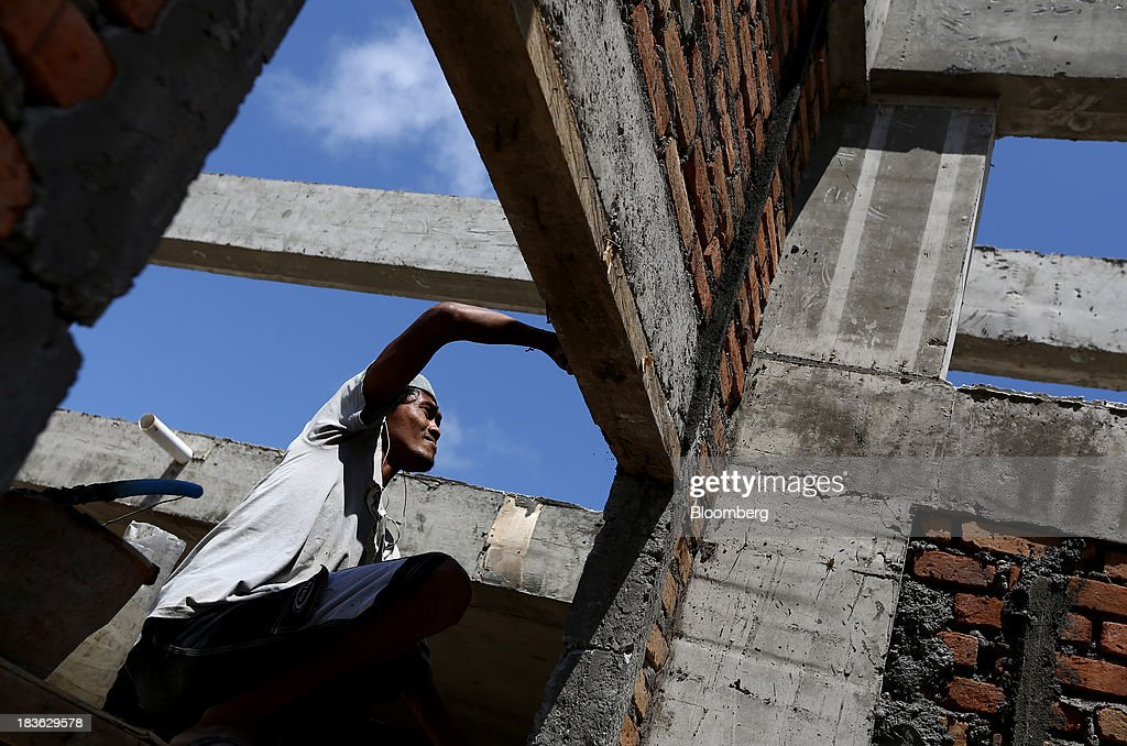 A worker labors on a residential construction site in Jimbaran, Bali, Indonesia, on Saturday, Oct. 5, 2013. Indonesia's central bank kept its key interest rate unchanged after its most aggressive tightening cycle in almost eight years as inflation pressure eased. Photographer: SeongJoon Cho/Bloomberg via Getty Images