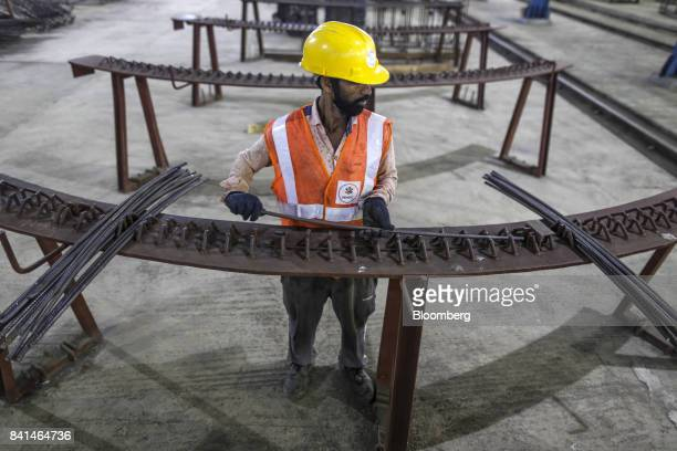A worker labors on the steel reinforcing of Precast concrete tunnel segments at the Mumbai Metro Rail Corp casting yard in Mumbai India on Monday Aug...