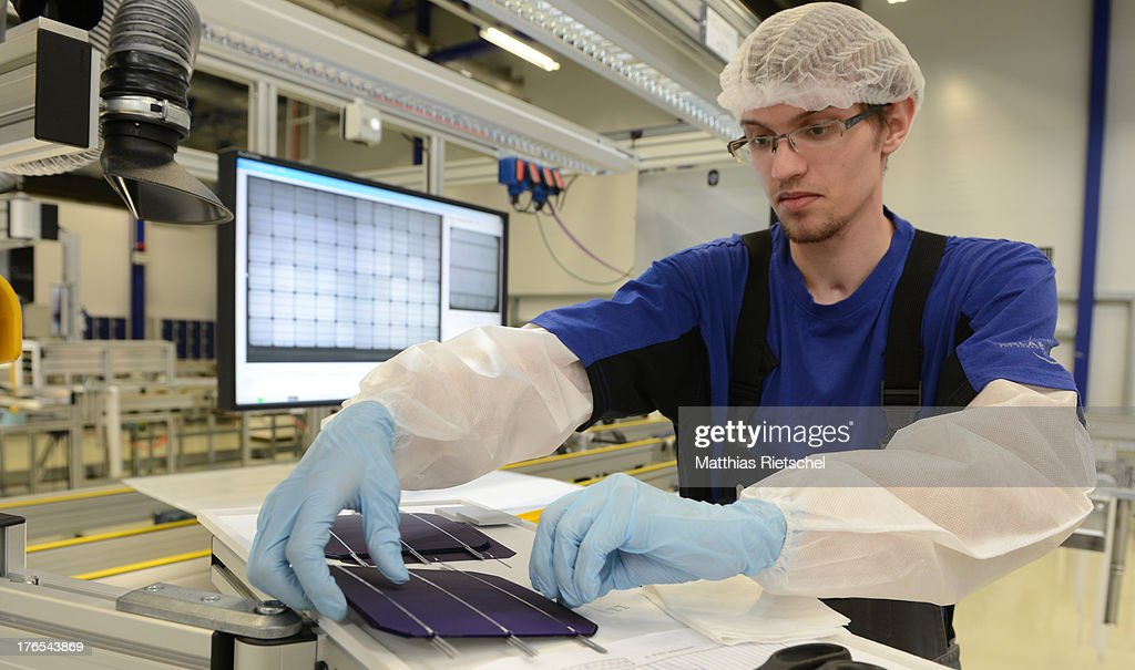 A worker laminates solar cells in the assembly line at the Solarworld plant on August 14, 2013 in Freiberg, Germany. The troubled solar cells, modules and panels producer managed to recently avoid bankruptcy by reaching an agreement with its shareholders and other investors. Many solar energy equipment producers in Germany are facing difficult times due to stiff competition from China.