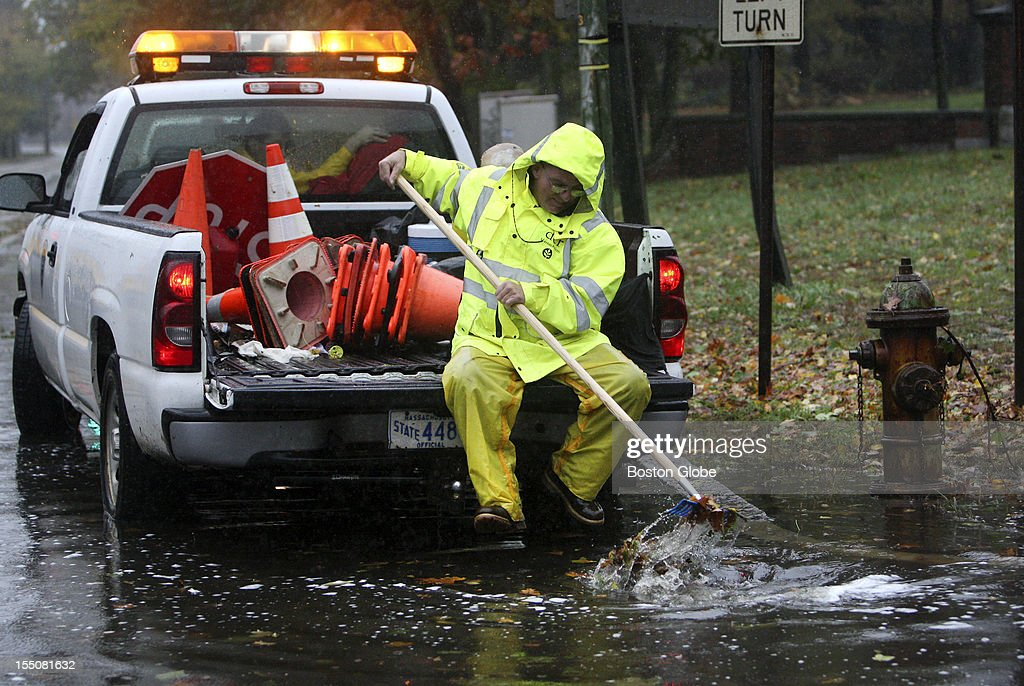 DCR worker Larry Callanan clears a storm drain on Mt. Auburn Street in Cambridge, Mass. as the area dealt with rains and winds caused by Hurricane Sandy, Oct. 29, 2012.