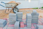 Worker laying red and gray concrete paving blocks. Road Paving, construction.