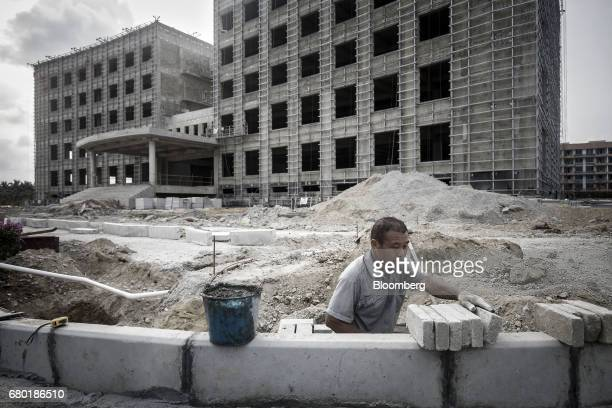 A worker lays bricks at the construction site of a China Stem Cell Group hospital inside the Hainan Boao Lecheng...