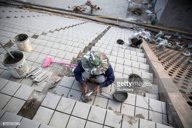 A worker lays floor tiles at a construction site in Vientiane Laos on Thursday Nov 2 2017 Located in the Mekong region Southeast Asia's frontier...