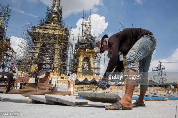 A worker lays paving slabs while preparing the ceremonial ground for King Bhumibol Adulyadej's cremation at Sanam Luang park in Bangkok Thailand on...