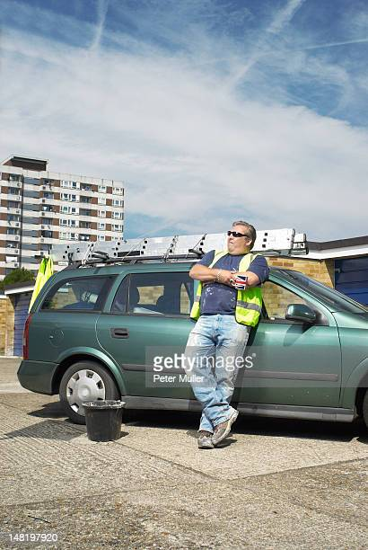 Worker leaning against car on site
