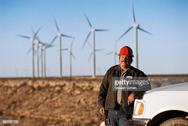 Worker leaning against truck with wind turbines in background