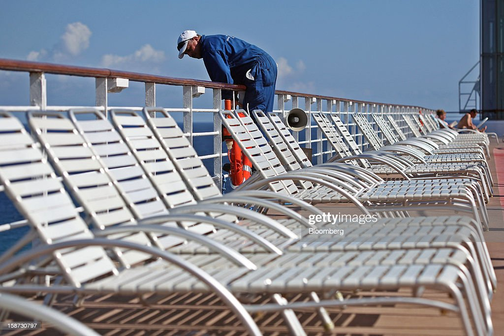 A worker leans over a railing behind empty white lounge chairs as he helps a fellow worker aboard Celebrity Cruises Inc.'s Constellation cruise ship while docked in Falmouth, Jamaica, on Monday, Dec. 17, 2012. Royal Caribbean Cruises Ltd. is a global cruise vacation company that operates Azamara Club Cruises, Celebrity Cruises, CDF Croisieres de France, Pullmantur Cruises and Royal Caribbean International. Photographer: Tim Boyle/Bloomberg via Getty Images