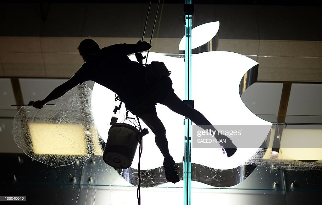 A worker leans to clean glass panels of the Apple store in the Central Business District of Sydney on Arpil 8, 2013. Australia economy grew 0.6 percent in the three months to December as exports lifted, but analysts have warned of a subdued picture overall. AFP PHOTO / Saeed Khan