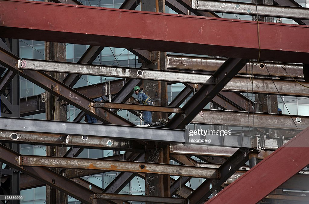 A worker, left, does welding on a steel beam at the construction site of the BBVA Bancomer Tower in Mexico City, Mexico, on Thursday, Dec. 13, 2012. The office for BBVA Bancomer, the Mexican unit of Banco Bilbao Vizcaya Argentaria SA, Spain's second-biggest bank, will have 50 floors and accommodate about 4,500 employees when it is completed. Photographer: Susana Gonzalez/Bloomberg via Getty Images