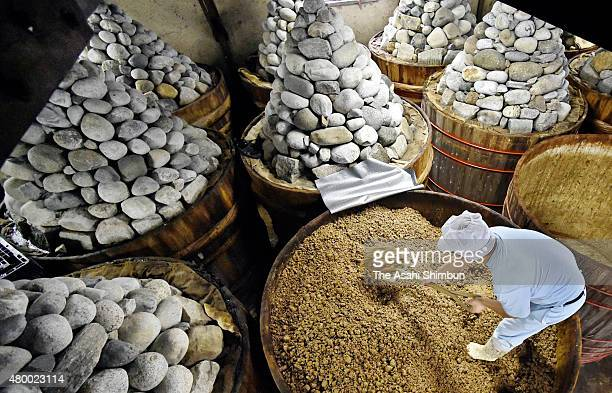A worker levels boild soybeans in a wooden tank as a process of producing Haccho Miso paste at the Maruya Haccho Miso factory on July 3 2015 in...