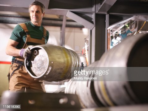 Worker lifting barrel in brewery