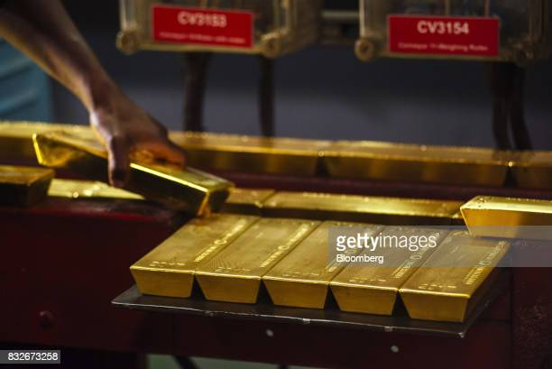 A worker lifts a gold bullion bar from a conveyor machine at the Rand Refinery Ltd plant in Germiston South Africa on Wednesday Aug 16 2017...