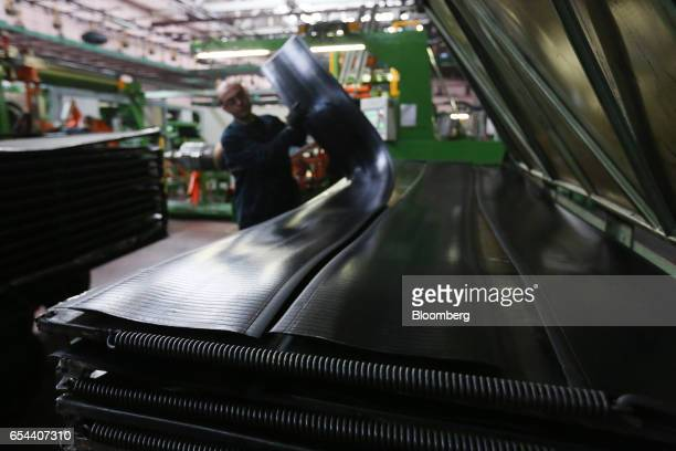 A worker lifts a length of rubber before the machine bonding process to form a tire at the Belshina JSC tire factory in Babruysk Belarus on Thursday...