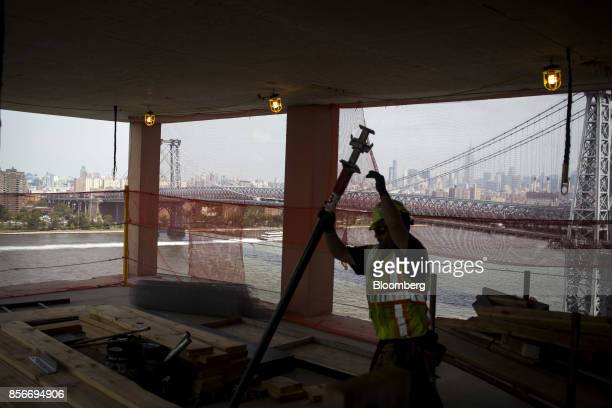 A worker lifts a pipe during construction at the 416 Kent Avenue apartment development in the Williamsburg neighborhood of the Brooklyn borough of...