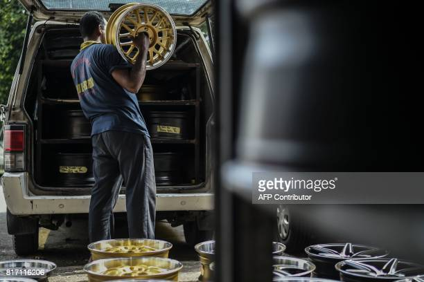 A worker lifts a refurbished alloy wheel into a van at a workshop in Ampang in the suburbs of Kuala Lumpur on July 18 2017 The workshop in the...