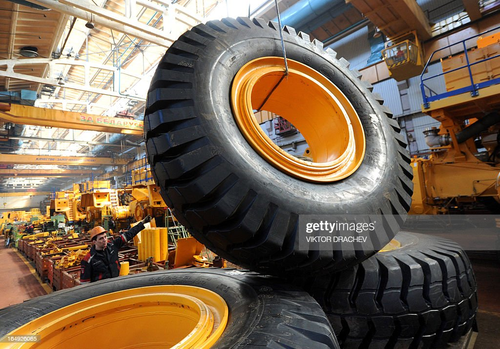 A worker lifts a wheel of heavy duty BelAZ dump-truck at the assembly department of the BelAZ automobile plant in the Belarus town of Zhodino, some 50km north of the capital Minsk, on March 29, 2013.
